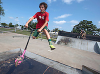 NWA Democrat-Gazette/J.T. WAMPLER Blain Whitfield of  Rogers performs a tail whip over the pyramid Thursday Aug. 6, 2015 on his scooter at the Rogers Skate Park. The first day of school is Aug. 17 for the Rogers school district.