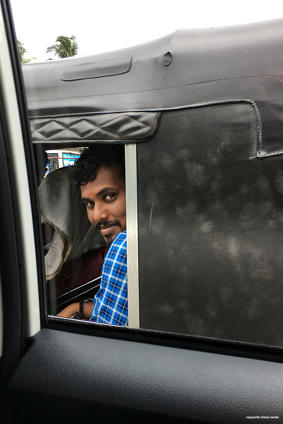 A man riding in an auto rickshaw smiles at me as I take a picture from the back seat window in Thiruvananthapuram, Kerala, India  June 17, 2017 (Cellphone Photo by Cheryl Senter)
