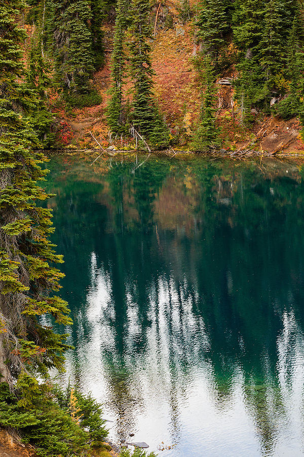 The still waters of Blue Lake reflect the image of the surrounding forest in Washington's North Cascade mountain range.