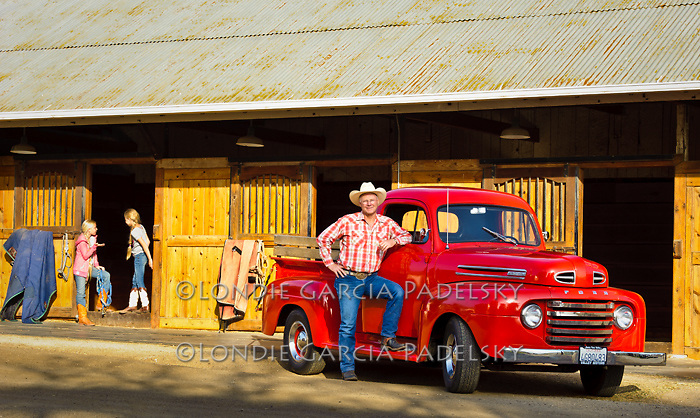 Cowboy and his 1949 Red Ford Truck parked at the horse stables on the ranch in San Luis Obispo, California (John Madonna)