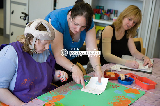 Day Service Officer is doing paperwork whilst care Assistant helps a service user,