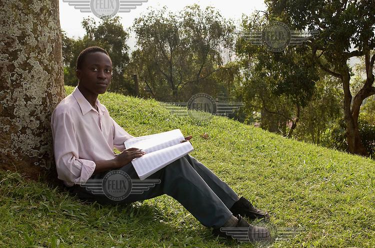 17-year-old student of the Kampala Music School, Tezigatwa, composing music on a hillside.