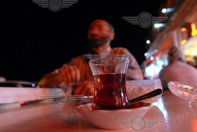 A glass of black, sweet Turkish tea at a bus stop in the middle of the night.