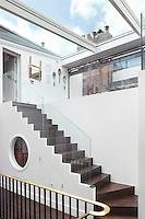A staircase leads up and into the modern top floor extension