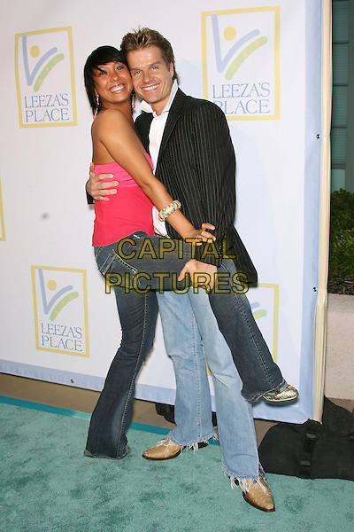 CHERYL BURKE & LOUIS VAN AMSTEL.Opening of Assistance League Leeza's Place Care Center in Hollywood, Los Angeles, California, USA,.21 April 2006..full length funny leg up holding leg.Ref: ADM/ZL.www.capitalpictures.com.sales@capitalpictures.com.©Zach Lipp/AdMedia/Capital Pictures.