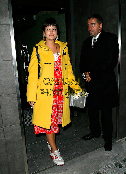 LILY ALLEN.Leaving Jimmy Choo's 10th Anniversary Party during London Fashion Week, Tamarai, Drury Lane, London, England, September 18th 2006..full length yellow duffel coat duffle red dress trainers nike fringe polka dot.Ref: AH.www.capitalpictures.com.sales@capitalpictures.com.©Adam Houghton/Capital Pictures.