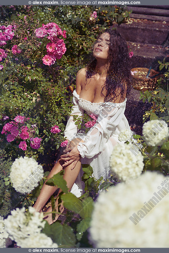 Sensual romantic photo of a beautiful sexy young woman in a wet summer dress with a wet dark long hair sitting on stairs in a rose garden enjoying the rain falling on her