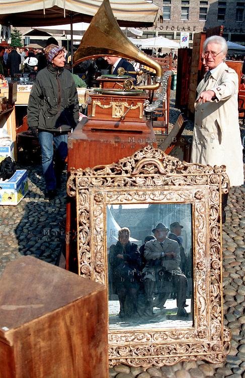 Pavia, mercato di antiquariato. Una coppia di anziani riflessa in uno specchio e un grammofono --- Pavia, antiques market. An elderly couple in a mirror and a gramophone