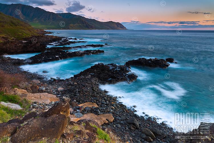 Sunset settles over the rocky shoreline of a beach in Makaha, O'ahu.