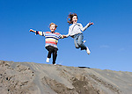 Aurora Alexander, age 7 and Sophie Marshall age 8 jumping off sand dune near Potholes Reservoir in Grant County, Washington