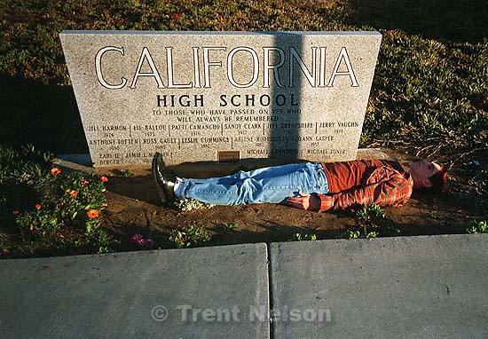 Tom McMahon laying in front of the &quot;dead people&quot; plaque at California High School.; San Ramon, CA<br />