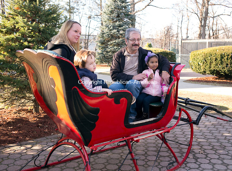 Torrington, CT- 06 December 2015-120615CM13-  Michelle Garceau, Jacob Buckley, 3,  Fred Shekohi, top right with, Samara Henaroo, 4 all of Torrington have their photo taken inside a sleigh at the Christmas Village in Torrington on Sunday.    Christopher Massa Republican-American