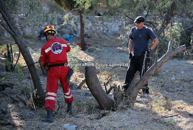 Pictured: Special forensics police officers and a Red Cross worker fell a tree after to make space for a further search by a disused building in a field in Kos, Greece. Saturday 01 October 2016<br /> Re: Police teams led by South Yorkshire Police, searching for missing toddler Ben Needham on the Greek island of Kos have moved to a new area in the field they are searching.<br /> Ben, from Sheffield, was 21 months old when he disappeared on 24 July 1991 during a family holiday.<br /> Digging has begun at a new site after a fresh line of inquiry suggested he could have been crushed by a digger.