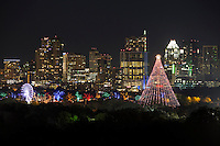 Zilker tree and the Trail of Lights illuminate the night sky against the Austin skyline .