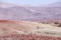 Morocco.  Man Riding Bicycle near Ait Benhaddou Ksar, a World Heritage Site.