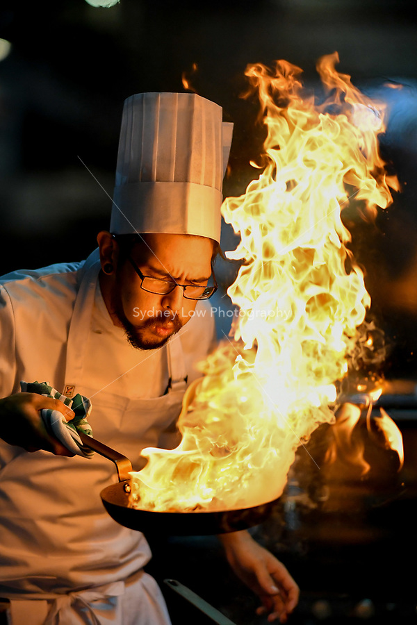 Melbourne, 30 May 2017 - Tyson Kromhout of the Salsa Bar & Grill in Port Douglas reacts to flames from his fry pan at the Australian selection trials of the Bocuse d'Or culinary competition held during the Food Service Australia show at the Royal Exhibition Building in Melbourne, Australia. Photo Sydney Low