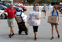 NWA Democrat-Gazette/DAVID GOTTSCHALK  Martin Trudell (from left), of Farmington, receives help Thursday, August 10, 2017, from Lauren Love and Heather Obermiller, sophomores at the University of Arkansas and both volunteers with Panhellenic Recruitment 2017, move items into campus housing for his twin daughters in Fayetteville. Students, including those in the University band and participating in sorority recruitment, had the opportunity to move in early.