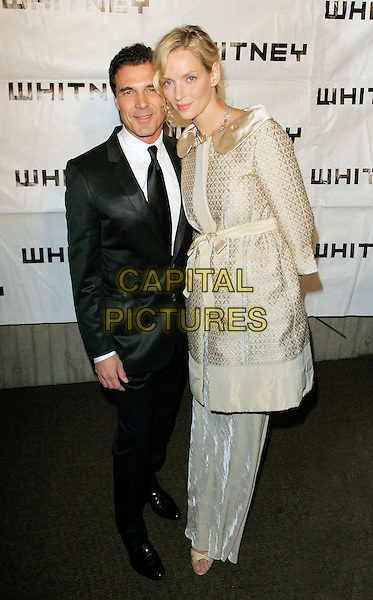 ANDRE BALASZ & UMA THURMAN.At the 2006 Whitney Gala Celebrating Picasso and American Art, New York, NY, USA, 23 October 2006..full length gold satin belted coat white dress skirt collar Louis Vuitton couple funny looks like arm is missing! no arm hand.Ref: ADM/JL.www.capitalpictures.com.sales@capitalpictures.com.©Jackson Lee/AdMedia/Capital Pictures.