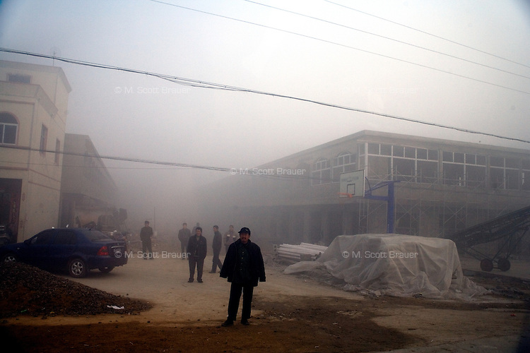 Men stand in the middle of a road on a foggy day in a small town in rural Jiangsu province, China.