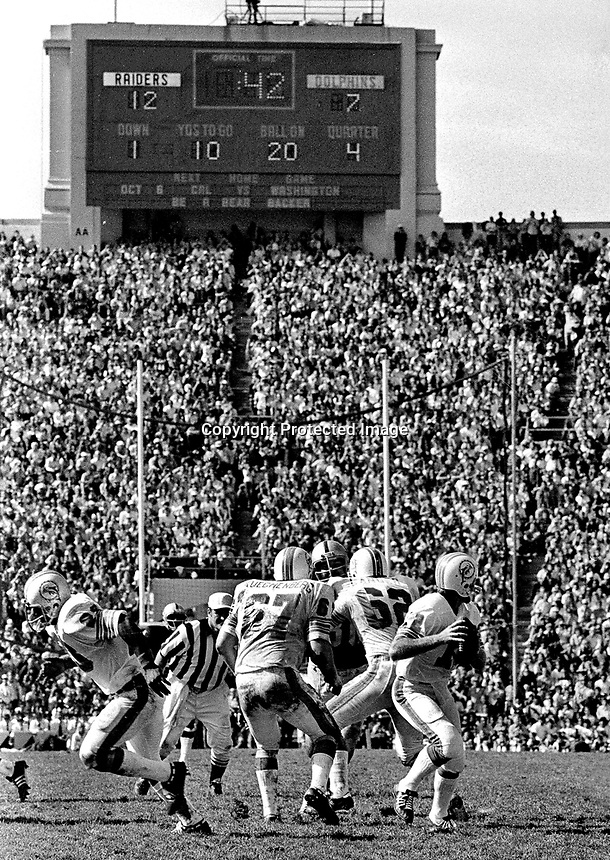 The scoreboard clock at U.C. Berkeley shows 42 seconds as Bob Griese drops back to pass...Miami lost to the Oakland Raiders 8 to 12..to snap the Dolphins 18 game win streak...(photo Sept 23,1973    by Ron Riesterer)