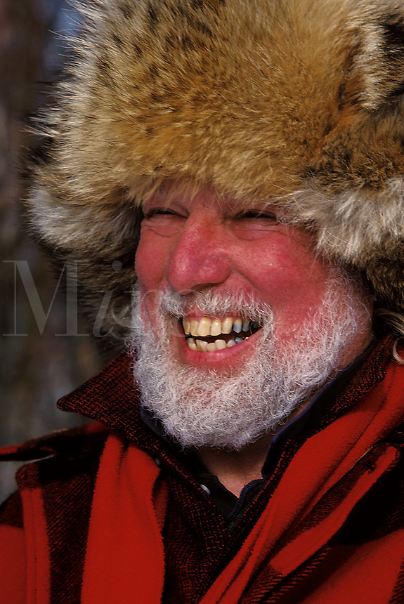 Portrait of a laughing man in a beard and fur hat. Alaska.