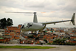 A Robinson 44 chopper flies over the slums of Sao Paulo's suburbia.