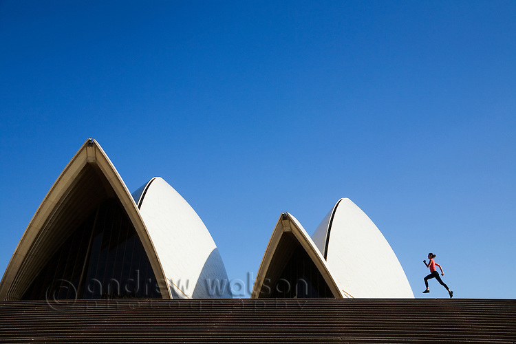 A woman runs along the steps of the Sydney Opera House.  Sydney, New South Wales, AUSTRALIA.