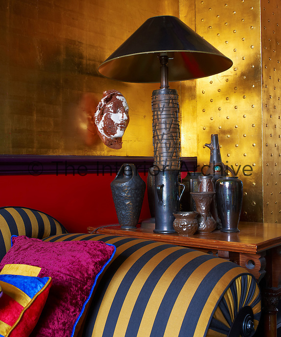 The walls of the living room are covered in gold leaf which casts a warm glow over the colourful furniture