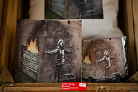 Pictured: The Banksy graffiti on a garage in Port Talbot made into merchandise in Sunrays Portalbot, Wales, UK. Friday 11 January 2019<br /> Re: A Banksy artwork, on the side of a garage in Port Talbot in December, has been sold privately for a six-figure sum.<br /> Season's Greetings was sold to Essex-based gallery owner John Brandler, who said he will keep the graffiti work in the town for a minimum of 2-3 years.<br /> About 20,000 people are thought to have visited the artwork in the past month.<br /> Steelworker Ian Lewis, who originally owned the artwork, said the sale was a weight off his shoulders.