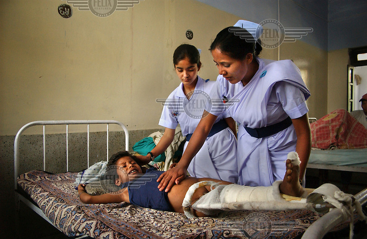 Nurses tend to nine year old Sunil Sharma in hospital. She was injured in an explosion as government forces battled with Maoist insurgents.