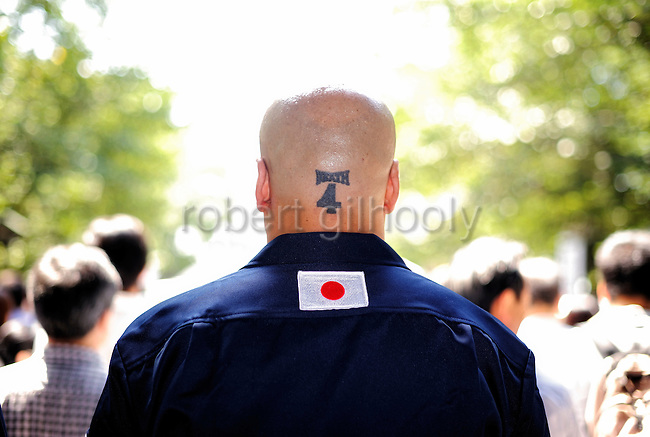 """Shinichi Kamijo, founder of ultra-rightwing group Gishin Gokoku-kai, shows off his tatoo -- the number 4 (""""shi"""" in Japanese and a homonym that also means """"death"""") and DEATH -- as he waits to offer prayer at Yasukuni Shrine in Tokyo on Saturday 15 Aug. 2009. Aug. 15 marks the 64th anniversary of Japan's surrender in the Pacific War."""