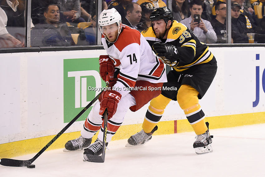 Thursday, March 10, 2016: Boston Bruins left wing Matt Beleskey (39) reaches around Carolina Hurricanes defenseman Jaccob Slavin (74) to poke the puck during the National Hockey League game between the Carolina Hurricanes and the Boston Bruins held at TD Garden, in Boston, Massachusetts. Carolina beats Boston 3-2 in overtime. Eric Canha/CSM
