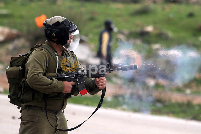 An Israeli security fires a tear gas canister towards Palestinian students from the University of Birzeit during clashes following a demonstration in support of Palestinian prisoners on hunger strike in Israeli jails, outside Israel's Ofer military prison, near the West Bank city of Ramallah, on February 12, 2013. Photo by Issam Rimawi