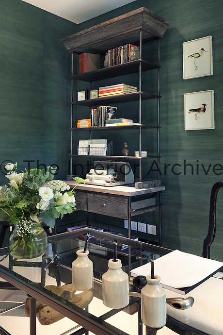 A glass topped desk in the study, with stained wood shelving and green papered walls