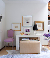 A white living room with a mix of modern and traditional furniture. A period style chair with lilac upholstery stands next to a simple white table with an ottoman below.