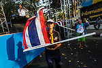 """01 FEBRUARY 2014 - BANGKOK, THAILAND: An anti-government protestor twirls a Thai flag after the polls were declared closed near the Din Daeng polling station in Bangkok. Thais went to the polls in a """"snap election"""" Sunday called in December after Prime Minister Yingluck Shinawatra dissolved the parliament in the face of large anti-government protests in Bangkok. The anti-government opposition, led by the People's Democratic Reform Committee (PDRC), called for a boycott of the election and threatened to disrupt voting. Many polling places in Bangkok were closed by protestors who blocked access to the polls or distribution of ballots. The result of the election are likely to be contested in the Thai Constitutional Court and may be invalidated because there won't be quorum in the Thai parliament.    PHOTO BY JACK KURTZ"""