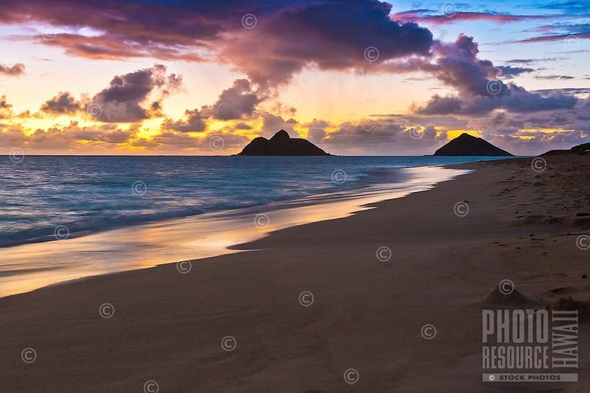 A colorful sunrise and the Mokulua Islets (or Islands), as seen from Lanikai Beach, Windward O'ahu.