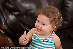 13 month old baby girl at home portrait smiling laughing looking to side with index finger pointing up horizontal