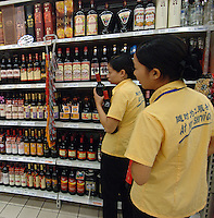 "Staff with the ""At Your Service"" uniform serving customers in the wine section in popular French supermarket chain Carrefour in Chengdu, China. Third quarter sales for the French brand were up 7.3% with China being one of the major areas of growth. Chengdu is one of western China's largest cities and the Government is encouraging investment with it's ""Go West"" campaign..24 Sep 2006"