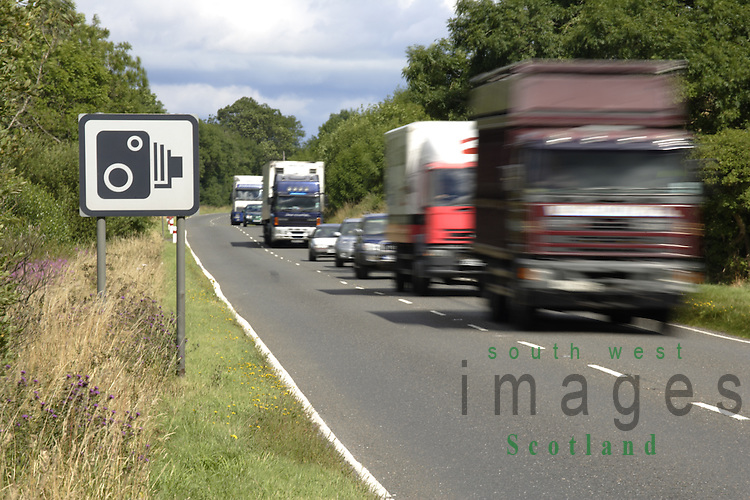 Speed camera sign on the A75 Dumfries to Stranraer road with traffic flying past UK