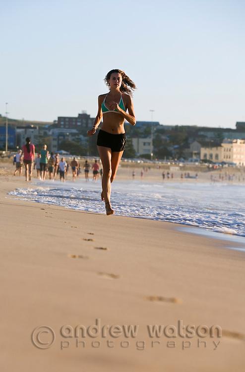 A woman jogging on the beach at Bondi.  Bondi Beach, Sydney, New South Wales, AUSTRALIA.
