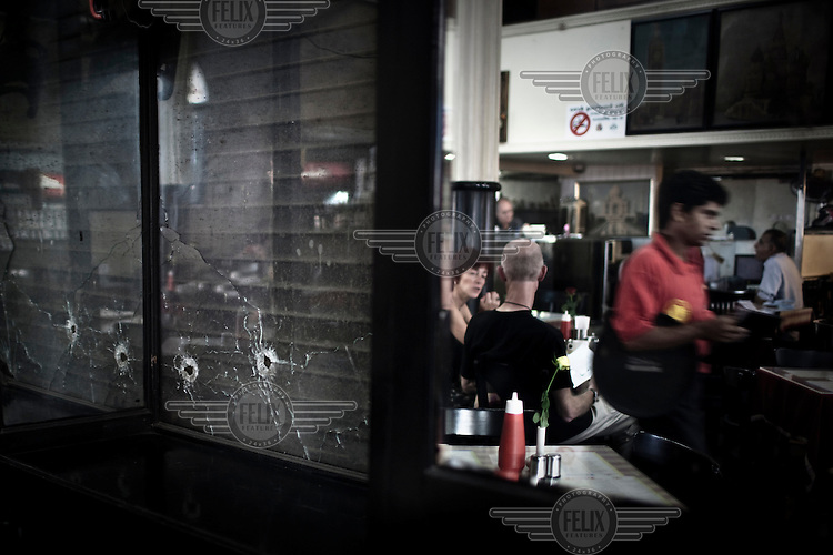 Customers at the Leopold Cafe sit in front of a pane of glass which still bears the scars from the 26/11 terrorist attack. The bullet holes have been left as a reminder, one year after the attacks..