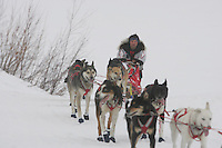 Ramey Brooks  runs up the bank of the Yukon river as he arrives at the Kaltag checkpoint.  2005 Iditarod Trail Sled Dog Race.