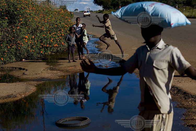 Children play around raw sewage as it flows through the streets of Bulawayo. Open sewers like this are largely responsible for the cholera epidemic that has struck the country.