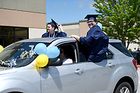 "Tristan Sarratt (from left) and William Clay ride by before receiving their diplomas, Sunday, May 17, 2020 during a graduation ceremony at the Northwest Arkansas Classical Academy in Bentonville. Northwest Arkansas Classical Academy hosted a graduation ceremony -- actually, a ""graduation convoy"" for its 17 seniors. Teachers and families parked throughout the parking lot. Seniors drove slowly through the lot while teachers and family members honked and waved to celebrate them. At the end of the route, headmaster Susan Provenza gave seniors their diplomas. Visit nwaonline.com/200518Daily/ for today's photo gallery.<br /> (NWA Democrat-Gazette/Charlie Kaijo)"