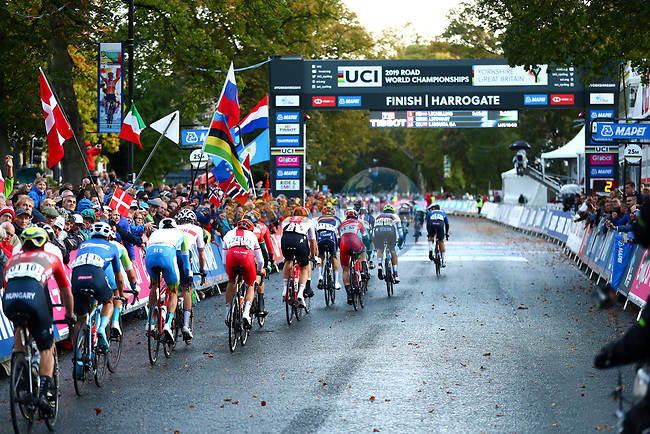 The peloton pass under the finish banner during the Men U23 Road Race of the UCI World Championships 2019 running 186.9km from Doncaster to Harrogate, England. 27th September 2019.<br /> Picture: Alex Whitehead/SWpix.com | Cyclefile<br /> <br /> All photos usage must carry mandatory copyright credit (© Cyclefile | Alex Whitehead/SWpix.com)