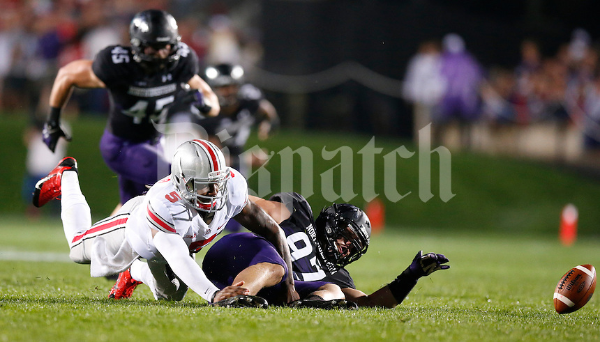 Ohio State Buckeyes quarterback Braxton Miller (5) fumbles the football as he is tackled by Northwestern Wildcats defensive lineman Tyler Scott (97) during Saturday's NCAA Division I football game at Ryan Field in Evanston on October 5 2013. (Barbara J. Perenic/The Columbus Dispatch)