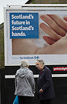 People talking in the street under a pro-Scottish independence poster in Baillieston, near Glasgow on the day that Scotland voted in the independence referendum. Yes Scotland were campaigning for the country to leave the United Kingdom, whilst Better Together were campaigning for Scotland to remain in the UK. On the 18th of September 2014, the people of Scotland voted in a referendum to decide whether the country's union with England should continue or Scotland should become an independent nation once again and leave the United Kingdom.