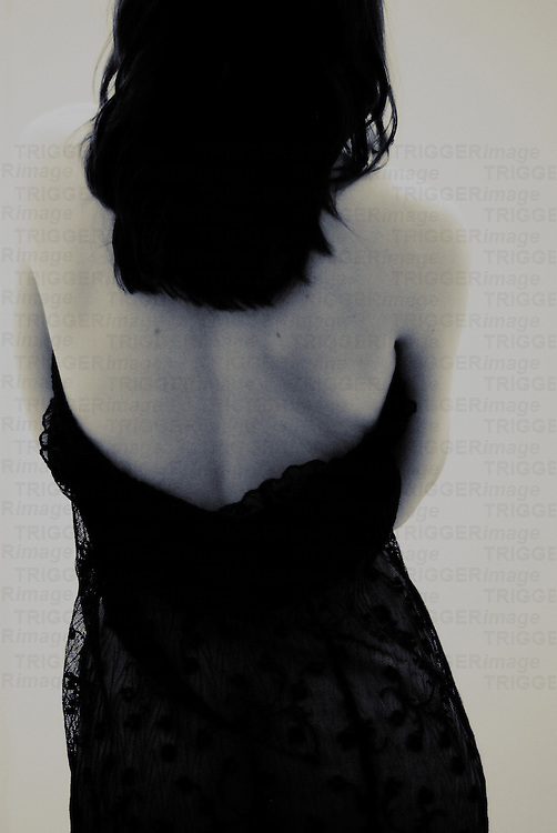 The bare back of a young woman with dark hair wearing a black dress