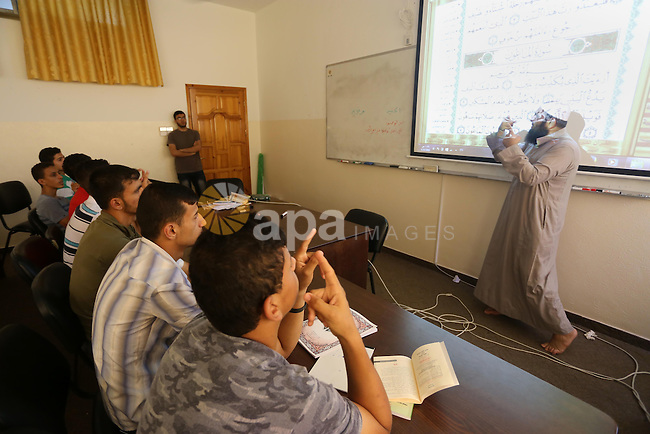 A Palestinian imam uses sign-language to teach the Koran, Islam's holy book, to deaf students at a religion school in Gaza City on June 21 2016, during the Muslim fasting month of Ramadan. Photo by Mohammed Asad